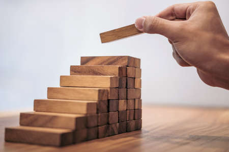 Foto für Alternative risk concept, plan and strategy in business, Risk To Make Business Growth Concept With Wooden Blocks, hand of man has piling up and stacking a wooden block. - Lizenzfreies Bild