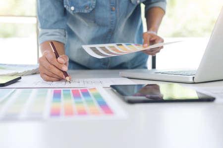 Foto de Creative creativity graphic designer working with graphics tablet,laptop and smart phone, colour chart at workplace on wooden desk , colour ideas style concept. - Imagen libre de derechos
