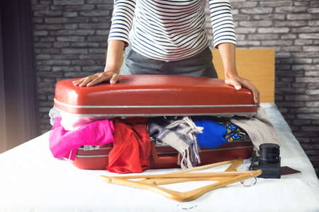 Photo for Travel and vacation concept, happiness young woman packing a lot of her clothes and stuff into suitcase on bed prepare for travel and journey trip in holiday. - Royalty Free Image