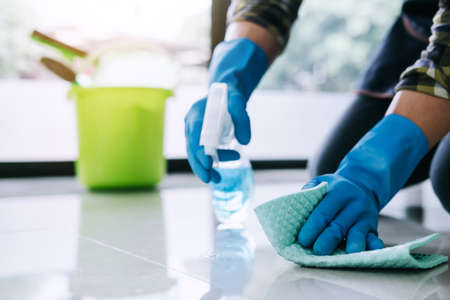 Foto de Husband housekeeping and cleaning concept, Happy young man in blue rubber gloves wiping dust using a spray and a duster while cleaning on floor at home. - Imagen libre de derechos