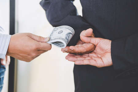 Photo for Bribery and corruption concept, bribe in the form of dollar bills, Businessman giving money while making deal to agreement. - Royalty Free Image