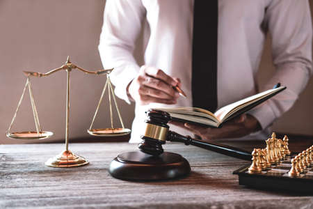 Foto de Gavel on wooden table and Lawyer or Judge working with agreement in Courtroom theme, Justice and Law concept. - Imagen libre de derechos