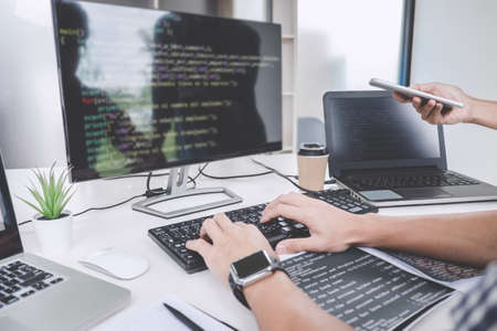 Foto de Programmers cooperating at Developing programming and website working in a software develop company office, writing codes and typing data code. - Imagen libre de derechos