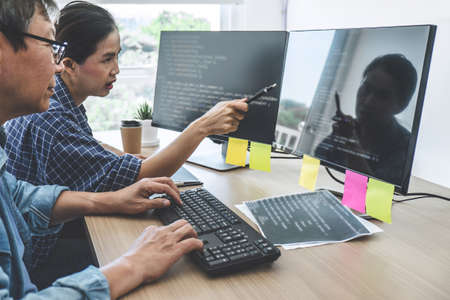 Foto de Two professional programmers cooperating at Developing programming and website working in a software develop company office, writing codes and typing data code. - Imagen libre de derechos