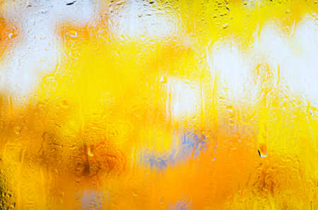 Yellow autumn maple leaves through the glass in drops