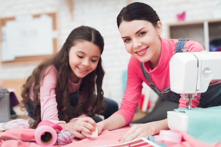 Photo for Mom and little daughter together sew clothes. They are in the sewing workshop. They are in a good mood. - Royalty Free Image
