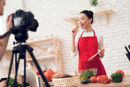 Photo for Two culinary bloggers in red aprons tasting salad with one girl behind camera. - Royalty Free Image