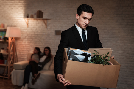 Photo pour Businessman leaves house with stuff box. Father leaves home because of problems in family. Family problems. Businessman is carrying box. - image libre de droit