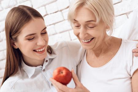 Foto de Girl is nursing elderly woman in bed at home. They are embracing. Woman is holding apple. - Imagen libre de derechos