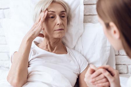 Foto de Girl is nursing elderly woman in bed at home. They are holding hands. Woman is feeling bad. - Imagen libre de derechos