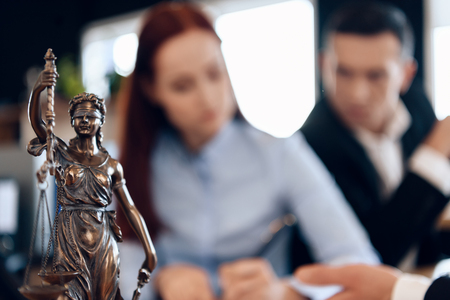 Photo for Bronze statue of Themis holds scales of justice. In unfocused background, couple signs documents. Couple going through divorce signing papers. - Royalty Free Image