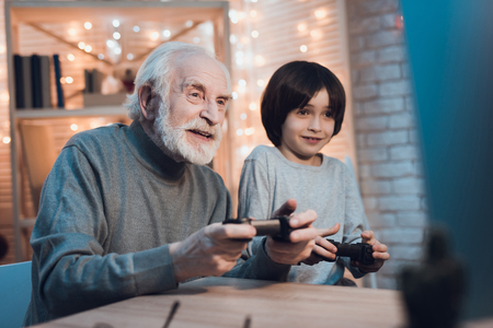 Foto de Grandfather and grandson are playing video games on computer at table at night at home. - Imagen libre de derechos
