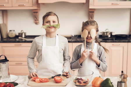 Foto de Children at kitchen table in kitchen. Brother and sister are playing with vegetables. - Imagen libre de derechos