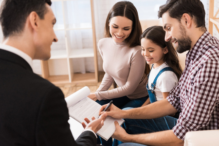 Foto de Young family signs business associate agreement to buy house together with realtor. Concept of real estate sales. Concept of house buying. - Imagen libre de derechos