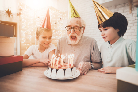 Foto de Grandfather, grandson and granddaughter at table at home. Grandpa is blowing candles on birthday cake. - Imagen libre de derechos
