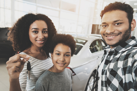 Photo pour African american family at car dealership. Mother, father and son are taking selfie with keys for new grey car. - image libre de droit
