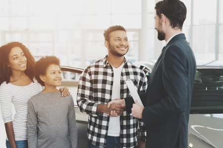 Photo pour African american family at car dealership. Salesman and man shaking hands, congratulating with new grey car. - image libre de droit