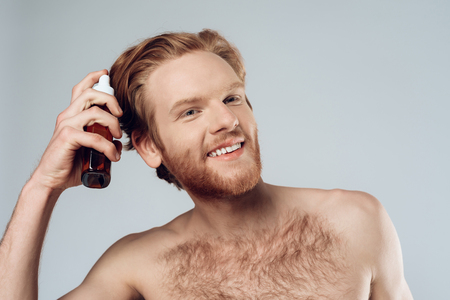 Foto de Red haired hairy man sprinkles balm on hair. Hair care. Isolated on grey background. Studio portrait. Male beauty concept. - Imagen libre de derechos
