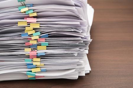 Photo pour Pile of documents with colorful clips on desk stack up - image libre de droit