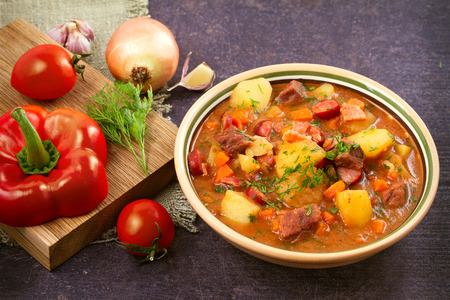 Photo for Tasty stew. Goulash soup bograch in a bowl and ingredients. Hungarian dish, horizontal - Royalty Free Image