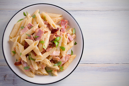 Photo pour Penne pasta with bacon and sundried tomatoes. Alfredo penne pasta on white plate on wooden table. overhead, horizontal - image libre de droit