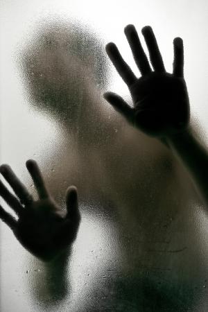 Foto de Dark Silhouette of a man with hands on a frosted glass - Imagen libre de derechos