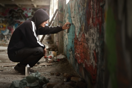 Photo for Illegal Young man Spraying black paint on a Graffiti wall. (room for text) - Royalty Free Image