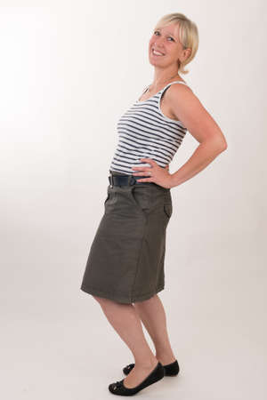 Foto de portrait of a attractive blond haired mid aged european woman wearing green skirt and blue white striped topshowing happy face - full body - studio shot on white background. - Imagen libre de derechos