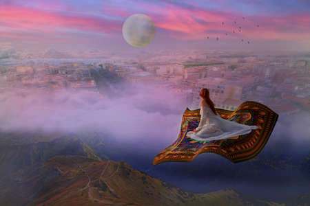 Photo for Young woman in a wedding dress flying on a carpet above clouds and city - Royalty Free Image