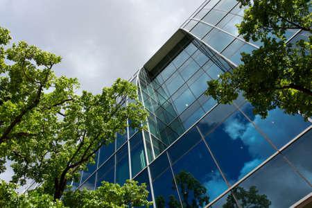Foto de Office building surrounded by alot of trees under blue sky - Imagen libre de derechos