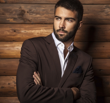 Foto de Portrait of young beautiful fashionable man against wooden wall   - Imagen libre de derechos