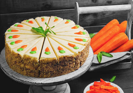 Photo pour Carrot cake pie, sprinkled with nuts, decorated with cream-colored carrots on a stand for cakes, fresh carrots in a white box on a dark black background wooden table in rustic style - image libre de droit