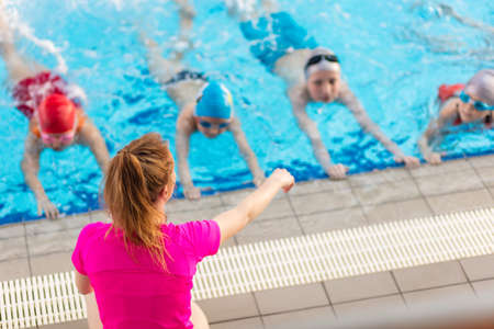 Foto de happy children kids group at swimming pool class learning to swim - Imagen libre de derechos