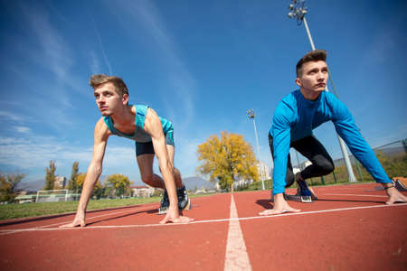 Photo pour Athletes at the sprint start line in track and field - image libre de droit