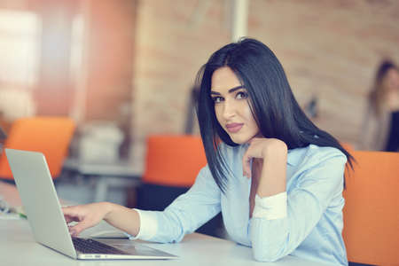 Photo for Image of woman using laptop while sitting at her desk. - Royalty Free Image