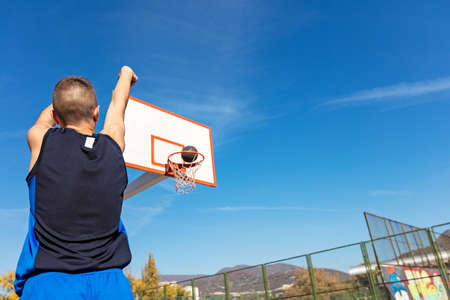 Photo pour Young man shooting free throws from the foul line - image libre de droit