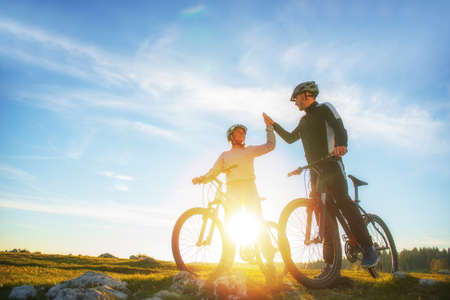 Foto de happy couple goes on a mountain road in the woods on bikes with helmets giving each other a high five - Imagen libre de derechos
