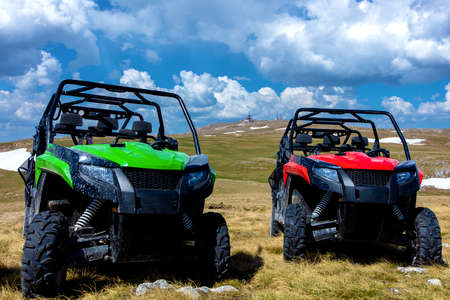 Photo pour Parked ATV and UTV, buggies on mountain peak with clouds and blue sky in background - image libre de droit