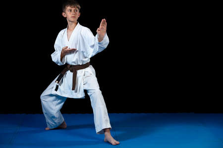 Photo for Young boy training karate on black background - Royalty Free Image