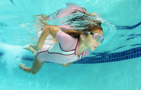 Photo for cute kid swimming underwater in pool - Royalty Free Image