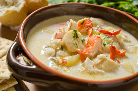 A steaming hot bowl of seafood chowder with lobster, clams, haddock, scallops, and potato.