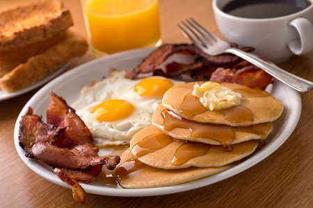 Photo for A delicious home style breakfast with crispy bacon, eggs, pancakes, toast, coffee, and orange juice. - Royalty Free Image