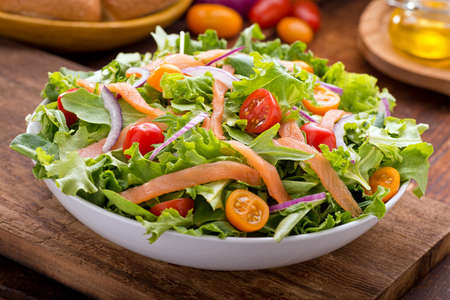 Photo for A delicious smoked salmon garden salad with smoked salmon, mixed baby greens, red and yellow cherry tomatoes and red onion with balsamic vinaigrette. - Royalty Free Image