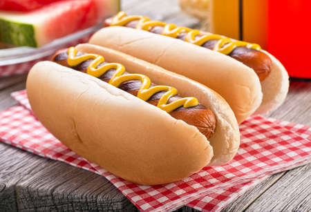 Photo for Delicious barbecued hot dogs on a rustic picnic table. - Royalty Free Image