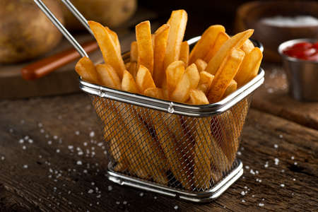 Photo for Crispy delicious french fries in a fryer basket. - Royalty Free Image