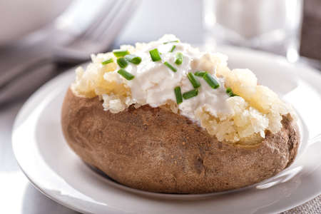 Photo for A delicious oven baked potato with sour cream and chives. - Royalty Free Image