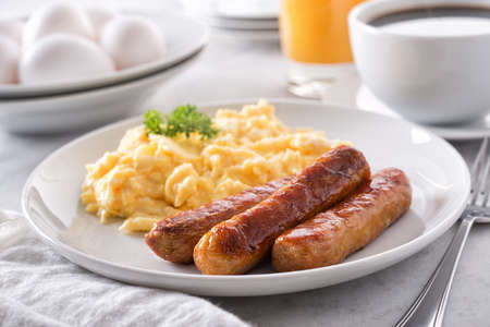 Photo for A plate of delicious scrambled eggs and breakfast sausage with coffee and orange juice. - Royalty Free Image