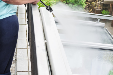 Photo pour Exterior cleaning and building cleaning a glass roof with high pressure water jet. - image libre de droit
