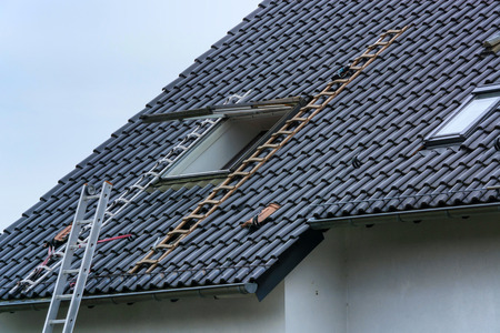 Photo pour Roofing, installation or repair of a roof window on a pitched roof - image libre de droit