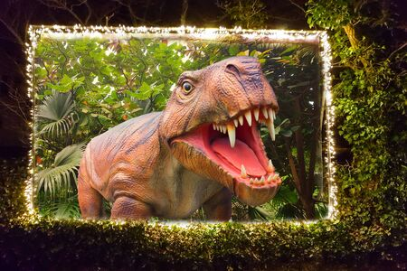 Photo pour Billboard framed in a hedge with a string of lights on which a dinosaur is depicted. With clipping path - image libre de droit